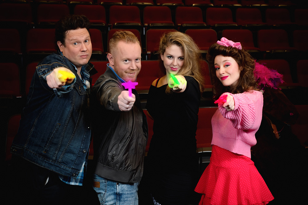 Photo of the cast of Seal Slippers in 80s costumes, holding magic wands at the camera.