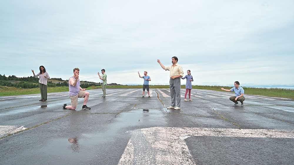 Seven dancers pose on paved airstrip.